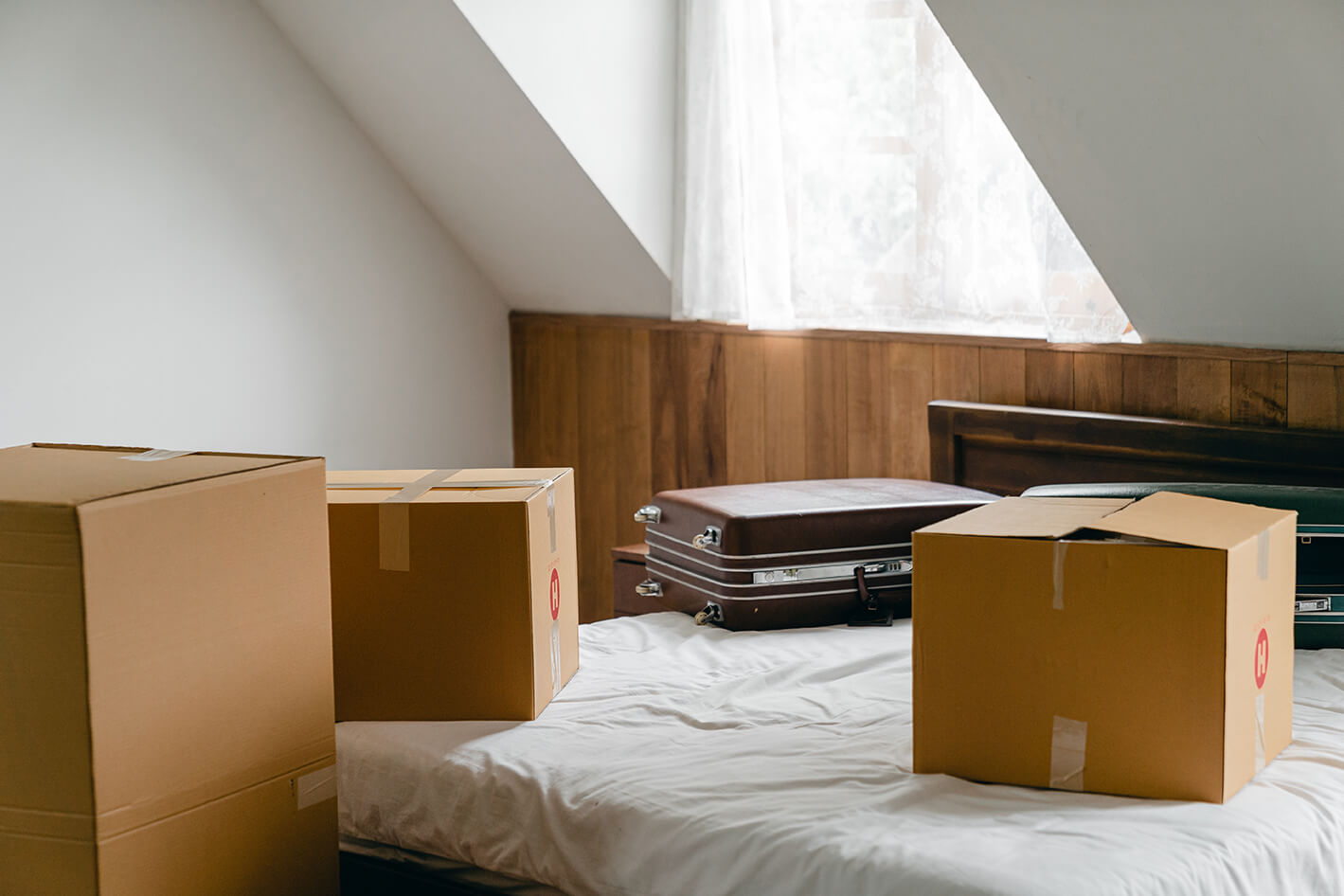carton-boxes-and-suitcases-placed-on-bed-in-empty-light-room-4246100
